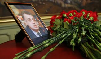 Flowers lay next to a portrait in memory of Russian Ambassador to Turkey Andrei Karlov, who was fatally shot by a Turkish policeman Monday in a gathering in Ankara, Turkey, before their talks on Syria in Moscow, Russia, Tuesday, Dec. 20, 2016. (Maxim Shemetov/Pool photo via AP)