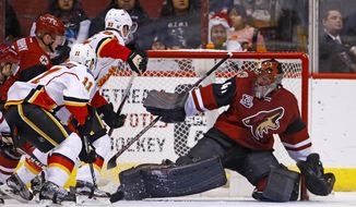 Calgary Flames center Mikael Backlund (11) scores a goal against Arizona Coyotes goalie Mike Smith (41) as Flames center Sam Bennett (93) creates a screen during the second period of an NHL hockey game Monday, Dec. 19, 2016, in Glendale, Ariz. (AP Photo/Ross D. Franklin)