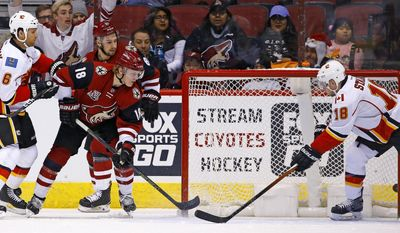 Arizona Coyotes center Christian Dvorak (18) scores a goal past Calgary Flames center Matt Stajan (18) and defenseman Dennis Wideman (6) while Coyotes right wing Josh Jooris (86) looks on during a first period of an NHL hockey game Monday, Dec. 19, 2016, in Glendale, Ariz. (AP Photo/Ross D. Franklin)