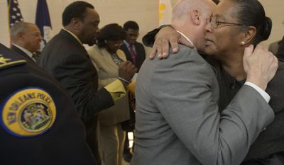 New Orleans Mayor Mitch Landrieu, center right, hugs Jackie Madison Brown, whose brother Ronald Madison was killed by New Orleans Police on the Danziger Bridge after Hurricane Katrina in 2005, after the mayor held a press conference to announce settlements in the civil rights cases, in New Orleans, La. Monday, Dec. 19, 2016. The city said it will pay out $13.3 million to 17 plaintiffs. Landrieu announced the city has reached settlements totaling $13.3 million in lawsuits over the deadly police shootings after Hurricane Katrina and a fatal beating just before the 2005 storm, and he apologized to the victims' families on behalf of the city. (Matthew Hinton/The Advocate via AP)