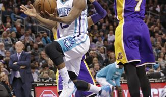 Charlotte Hornets' Kemba Walker, left, drives past Los Angeles Lakers' Larry Nance Jr., right, in the first half of an NBA basketball game in Charlotte, N.C., Tuesday, Dec. 20, 2016. (AP Photo/Chuck Burton)