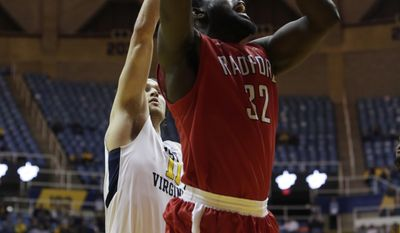 Radford center Randy Phillips (32) drives to the basket as West Virginia forward Nathan Adrian (11) attempts to block him from behind during the second half of an NCAA college basketball game, Tuesday, Dec. 20, 2016, in Morgantown, W.Va. (AP Photo/Raymond Thompson)