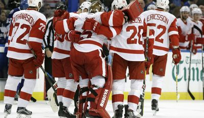 Detroit Red Wings goalie Jimmy Howard (35) is helped off the ice by his teammates after getting injured during the second period of an NHL hockey game against the Tampa Bay Lightning, Tuesday, Dec. 20, 2016, in Tampa, Fla. (AP Photo/Chris O'Meara)