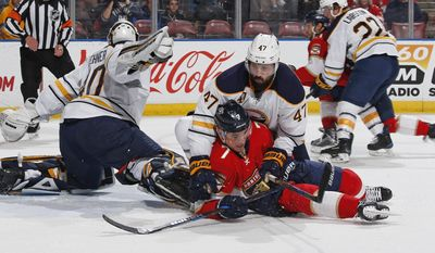 Buffalo Sabres defenseman Zach Bogosian (47) checks Florida Panthers center Colton Sceviour (7) in front of Buffalo Sabres goaltender Robin Lehner (40) during the first period of an NHL hockey game, Tuesday, Dec. 20, 2016, in Sunrise, Fla. (AP Photo/Joel Auerbach)