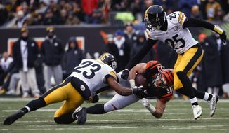 Cincinnati Bengals running back Rex Burkhead (33) dives for yardage against Pittsburgh Steelers free safety Mike Mitchell (23) and cornerback Artie Burns (25) in the first half of an NFL football game, Sunday, Dec. 18, 2016, in Cincinnati. (AP Photo/Frank Victores)