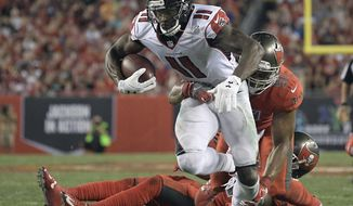 FILE - In this Nov. 3, 2016, file photo, Atlanta Falcons wide receiver Julio Jones (11) slips a tackle by Tampa Bay Buccaneers outside linebacker Daryl Smith (51) during the third quarter of an NFL football game, in Tampa, Fla. A healthy Julio Jones could provide the boost the Falcons need as they try to win the NFC South. After missing two games with a sprained toe, Jones is expected to try to run full speed on Wednesday as he tries to return in Saturday's game at Carolina. (AP Photo/Phelan Ebenhack, File)