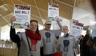 Opponents of House Bill 2 hold signs outside the  House chambers gallery as the North Carolina General Assembly convenes for a special session at the Legislative Building in Raleigh, N.C., Wednesday, Dec. 21, 2016. (Chris Seward/The News & Observer via AP) ** FILE **