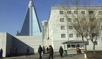 In this Dec. 11, 2016 photo, residents pass by the towering Ryugyong Hotel in Pyongyang, North Korea. Thirty years after work began on what was then one of the tallest hotel projects ever attempted, the inside of the structure has yet to be completed and mystery swirls over whether it ever will ever open for guests.  (AP Photo/Eric Talmadge)