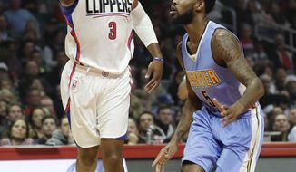 Los Angeles Clippers guard Chris Paul, left, shoots over Denver Nuggets guard Will Barton during the first half of an NBA basketball game in Los Angeles, Tuesday, Dec. 20, 2016. (AP Photo/Chris Carlson)