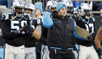 FILE - In this Dec. 11, 2016, file photo, Carolina Panthers' Luke Kuechly, center, cheers on his team in the second half of an NFL football game against the San Diego Chargers in Charlotte, N.C. While Kuechly desperately wants to play again this year, Carolina Panthers coach Ron Rivera is hesitant to risk putting him on the field and having the Pro Bowl linebacker risk another concussion. (AP Photo/Bob Leverone, File)