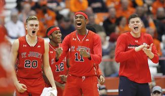 St. John's Richard Freudenberg, left, and teammate Tarig Owens, center, and others celebrate on the St. John's bench late in the second half of an NCAA college basketball game against Syracuse in Syracuse, N.Y., Wednesday, Dec. 21, 2016. St. John's won 93-60. (AP Photo/Nick Lisi)