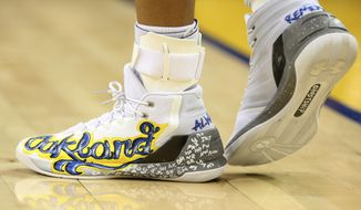 This Dec. 15, 2016 photo shows the shoes worn by Golden State Warriors' Stephen Curry that honor victims of a warehouse fire during an NBA basketball game against the New York Knicks in Oakland, Calif. Curry is auctioning off two special pairs of shoes to raise money for victims of the Oakland warehouse fire. (Ray Chavez/San Jose Mercury News via AP)