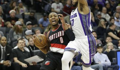 Portland Trail Blazers guard Damian Lillard, left, drives against Sacramento Kings guard Garrett Temple during the first quarter of an NBA basketball game Tuesday, Dec. 20, 2016, in Sacramento, Calif. .(AP Photo/Rich Pedroncelli)