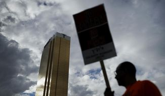 FILE - In this Sept. 21, 2016, file photo, Laborers' International Union of North America members and Culinary Union members protest outside of the Trump International hotel in Las Vegas. Union officials announced Wednesday, Dec. 21, 2016, that workers at the Trump International Hotel in Las Vegas reached a contract with management after pushing for negotiations for a year, while management at a Trump hotel in Washington, D.C. has agreed to allow a unionization campaign at that property. (AP Photo/John Locher, File)