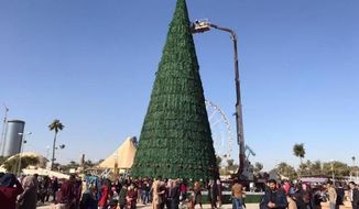 Workers use a crane to prepare a large Christmas tree in al-Zawra Park, Baghdad, Iraq. (Associated Press/Ali Abdul Hassan)