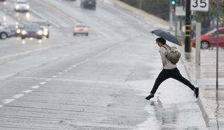 A pedestrian leaps over a puddle along La Paz Road in Victorville, Calif. on Thursday, Dec, 22, 2106. The forecast includes rain and possible snow through Saturday. (James Quigg/The Daily Press via AP)