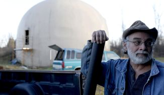 In this Nov. 29, 2016 photo, Wayne Price, 60, holds the blueprints of the 4,650 square feet concrete monolithic dome he was in the processes of building in Otisville, Mich. Financial realities have forced Price to abandon his dream of finishing, and living in, a dome home. Price is selling the unfinished monolithic domed structure for $150,000 after he estimates sinking roughly $200,000 in the project over 16 years (Tegan Johnston/The Flint Journal-MLive.com via AP)