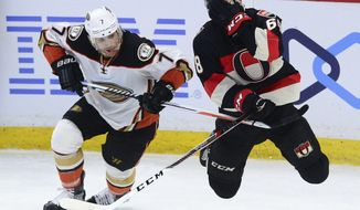 Ottawa Senators left wing Mike Hoffman holds his face after getting high-sticked from Anaheim Ducks left wing Andrew Cogliano during overtime in an NHL hockey game, Thursday, Dec. 22, 2016 in Ottawa, Ontario. The Senators defeated the Ducks 2-1. (Sean Kilpatrick/The Canadian Press via AP)