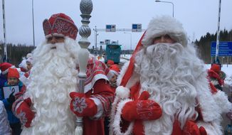 Finland's Santa, right, and Russia's Grandfather Frost meet at the two countries busiest joint border crossing  in Nuijamaa, Finland on Monday Dec. 19, 2016, as an annual show of goodwill and neighborly friendship. But despite the jovial ho-ho-hos in the annual show of seasonal goodwill and neighborly friendship, there lies an increasing disquiet in the Nordic nation. (AP Photo/Vitnija Saldava)