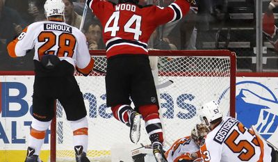 New Jersey Devils left wing Miles Wood (44) celebrates after scoring a goal against Philadelphia Flyers center Claude Giroux (28), goalie Steve Mason (35) and defenseman Shayne Gostisbehere (53) during the first period of an NHL hockey game, Thursday, Dec. 22, 2016, in Newark, N.J. (AP Photo/Julio Cortez)