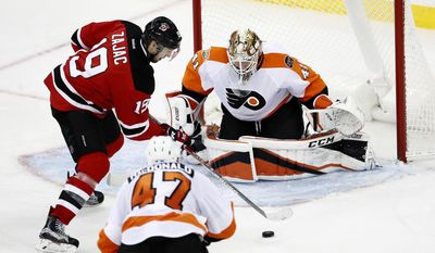 New Jersey Devils center Travis Zajac (19) attacks against Philadelphia Flyers goalie Anthony Stolarz (41) and defenseman Andrew MacDonald (47) during the third period of an NHL hockey game, Thursday, Dec. 22, 2016, in Newark, N.J. (AP Photo/Julio Cortez)
