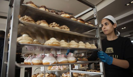 In this Thursday, Dec. 15, 2016 file photo, a bakery employee wheels doughnuts in Bnei Brak, Israel.  (AP Photo/Dan Balilty)