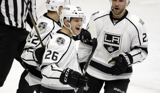 Los Angeles Kings center Nic Dowd (26) celebrates with Trevor Lewis (22) and Alec Martinez (27) after Dowd scored a goal against the Nashville Predators during the third period of an NHL hockey game Thursday, Dec. 22, 2016, in Nashville, Tenn. (AP Photo/Mark Humphrey)