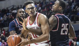 Mississippi forward Sebastian Saiz (11) is defended by South Alabama guard Ken Williams (1) and forward Don MuepoKelly (25) during an NCAA college basketball game in Oxford, Miss., on Thursday, Dec. 22, 2016. (Bruce Newman/Oxford Eagle via AP)