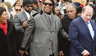 Motown legend Stevie Wonder walks down Milwaukee Street, a portion of which will soon be renamed Stevie Wonder Avenue, with Detroit City Council President Brenda Jones, far left, and Detroit Mayor Mike Duggan, far right, during a ceremony in Detroit on Wednesday, Dec. 21, 2016. (The Detroit News/ Daniel Mears/Detroit News via AP)