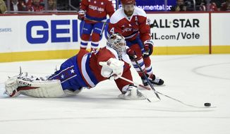 Washington Capitals goalie Braden Holtby (70) dives for the puck next to defenseman Brooks Orpik (44) during the second period of an NHL hockey game against the Tampa Bay Lightning, Friday, Dec. 23, 2016, in Washington. (AP Photo/Nick Wass)
