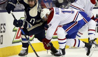 Columbus Blue Jackets forward Brandon Dubinsky, left, passes the puck against Montreal Canadiens forward Torrey Mitchell during the second period of an NHL hockey game in Columbus, Ohio, Friday, Dec. 23, 2016. (AP Photo/Paul Vernon)