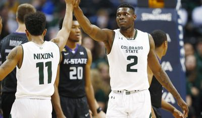 In this Saturday, Dec. 17, 2016, photo, Colorado State guard Prentiss Nixon, left, congratulates forward Emmanuel Omogbo after he scored a basket and drew a foul by Kansas State during an NCAA college basketball game in Denver. Omogbo has written tributes to his parents, Samson and Caroline, and his sisters' twins, Israel and Anna, on the heel caps of his basketball shoes to honor the four family members who died in a house fire in Maryland on Jan. 19 of this year. (AP Photo/David Zalubowski)