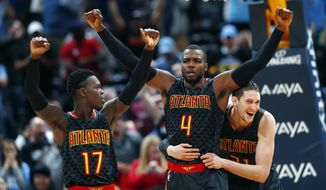 Atlanta Hawks forward Paul Millsap, center, celebrates with guard Dennis Schroder, left, of Germany, and forward Mike Muscala as time runs out in the second half of an NBA basketball game against the Denver Nuggets, Friday, Dec. 23, 2016, in Denver. The Hawks won 109-108. (AP Photo/David Zalubowski)