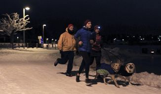 In this Tuesday, Dec. 14, 2016, photo, runners and dogs jog on a trail at Westchester Lagoon in Anchorage, Alaska. With ice present on city streets for up to seven months per year, most walkers and runners use footwear that has built-in studs or attached cleats as a safety measure to avoid falling. (AP Photo/Dan Joling)