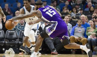 Minnesota Timberwolves forward Andrew Wiggins (22) and Sacramento Kings forward DeMarcus Cousins (15) go for a loose ball during the first half of an NBA basketball game, Friday, Dec. 23, 2016, in Minneapolis. (AP Photo/Paul Battaglia)