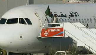 An Afriqiyah Airways plane stands on the tarmac at Malta International airport as an unidentified man waves a flag, Friday, Dec. 23, 2016. Hijackers diverted the Libyan commercial plane to Malta on Friday and threatened to blow it up with hand grenades, Maltese authorities and state media said. (TVM via AP)