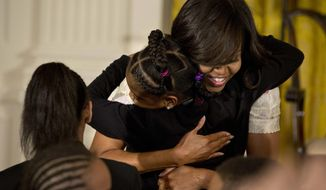 FILE - This April 20, 2016 file photo shows first lady Michelle Obama giving a hug to a child during the annual White House Take Our Daughters and Sons to Work Day event attended by the children of Executive Office employees, young people from Big Brothers Big Sisters of America, SchoolTalk, and the D.C. Child and Family Services Agency, in the East Room of the White House in Washington. The feel-good initiatives of first lady Michelle Obama have served as both inspiration and eight years of teaching moments for many families. (AP Photo/Jacquelyn Martin, File)