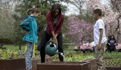 This April 15, 2015 file photo, first lady Michelle Obama waters a bed of vegetable seeds with students Nare Kande of the New York Botanical Gardens in the Bronx, N.Y., right, and Marley Santos of Foothill Elementary School in Boulder, Colo., left, during the seventh annual White House Kitchen Garden Planting on the South Lawn of the White House in Washington. (AP Photo/Carolyn Kaster, File)