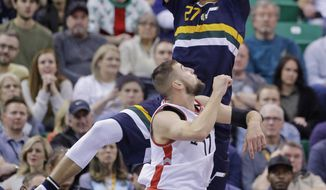 Utah Jazz center Rudy Gobert (27) pulls down a rebound as Toronto Raptors center Jonas Valanciunas (17) looks on in the first half during an NBA basketball game Friday, Dec. 23, 2016, in Salt Lake City. (AP Photo/Rick Bowmer)