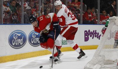 Florida Panthers defenseman Mark Pysyk (13) and Detroit Red Wings left wing Anthony Mantha (39) battle for control of the puck behind the net during the second period of an NHL hockey game, Friday, Dec. 23, 2016, in Sunrise, Fla. (AP Photo/Joel Auerbach)