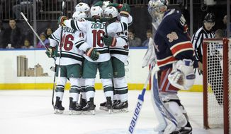 Minnesota Wild players celebrate a goal by Michael Granlund as New York Rangers goaltender Henrik Lundqvist stands in front of the net during the first period of an NHL hockey game Friday, Dec. 23, 2016, at Madison Square Garden in New York. (AP Photo/Bill Kostroun)