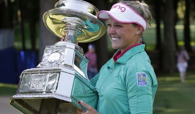 FILE - In this June 12, 2016 file photo, Brooke Henderson, of Canada, lifts the championship trophy after winning the Women's PGA Championship golf tournament at Sahalee Country Club in Sammamish, Wash. (AP Photo/Elaine Thompson, File)