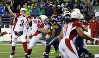 Arizona Cardinals quarterback Carson Palmer (3) passes to wide receiver Larry Fitzgerald, right, during the second half of an NFL football game, Saturday, Dec. 24, 2016, in Seattle. The Cardinals won 34-31. (AP Photo/Ted S. Warren)