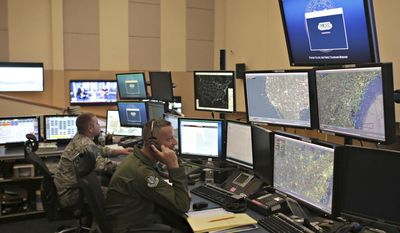 Members of the 601st Air Operations Center will watch Santa fly around the world on Christmas Eve with their NORAD Santa tracker on Friday, Dec. 23, 2016 in Panama City, Fla. (Heather Howard/News Herald via AP)