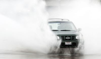A motorist driving an Isuzu hits a large puddle on W. Garden Grove Blvd. and Fairview St. as a warm weather front brings rain on Thursday morning, Dec. 22, 2016, in Garden Grove, Calif. (Ken Steinhardt/The Orange County Register via AP)