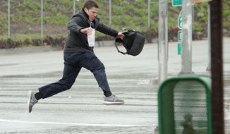 Jared Gaston, 25, of Santa Ana hesitated before jumping flooded Fairview Street to get to Starbucks to meet a friend as a warm weather front brings rain Thursday, Dec. 22, 2016, in Garden Grove, Calif. (Ken Steinhardt/The Orange County Register via AP)