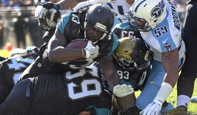 Jacksonville Jaguars running back Chris Ivory (33) scores a touchdown in front of Tennessee Titans inside linebacker Wesley Woodyard (59) during the first half of an NFL football game, Saturday, Dec. 24, 2016, in Jacksonville, Fla. (AP Photo/Phelan M. Ebenhack)
