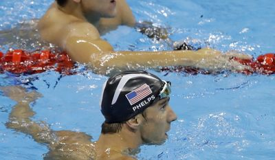 FILE - In this Aug. 12, 2016, file photo, United States' Michael Phelps, bottom, and Singapore's Joseph Schooling look at the clock at the end of the men's 100-meter butterfly swimming final at the Summer Olympics in Rio de Janeiro, Brazil. Schooling won his country's first gold medal with an upset victory in the 100-meter butterfly. Phelps finished in a three-way tie for second, giving him a silver to go along with five golds in what was again billed as his final Olympics. (AP Photo/Rebecca Blackwell, File)