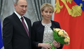 FILE - In this Thursday, Dec. 8, 2016 file photo, Russian President Vladimir Putin, left, stands with doctor Yelizaveta Glinka after giving her a state award at the award presentation ceremony for charity and human rights achievements in the Kremlin in Moscow, Russia. A Russian plane with 92 people aboard, including a well-known military band, crashed into the Black Sea on its way to Syria on Sunday, Dec. 25, minutes after takeoff from the resort city of Sochi, the Defense Ministry said. Glinka, widely known for her charity efforts, was among those on board the Tu-154 plane. Her foundation said she was accompanying a shipment of medicines for a Syrian hospital. (Alexei Nikolsky/Sputnik, Kremlin Pool Photo via AP, File)