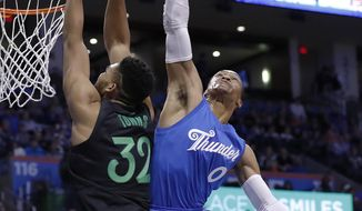 Minnesota Timberwolves center Karl-Anthony Towns (32) goes to the basket as Oklahoma City Thunder guard Russell Westbrook (0) defends during the first half of an NBA basketball game in Oklahoma City, Sunday, Dec. 25, 2016. (AP Photo/Alonzo Adams)